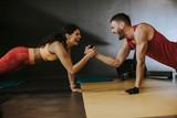 Dopasuj sprawny mężczyzna i kobieta robi ćwiczenia podstawowe deski