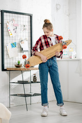 Full length view of teenager in jeans holding longboard at home