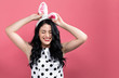 canvas print picture - Young woman with Easter rabbit ears on a pink background