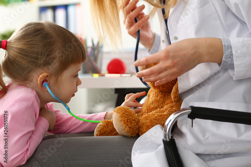 Leinwandbild Motiv Little girl hold in arms toy stethoscope playing with teddy bear while visiting doctor
