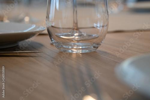 canvas print picture Wasserglas auf Holztisch mit Besteck und Teller
