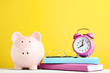 canvas print picture - Pink piggy bank with alarm clock, glasses and books on yellow background