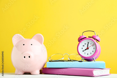 canvas print picture Pink piggy bank with alarm clock, glasses and books on yellow background