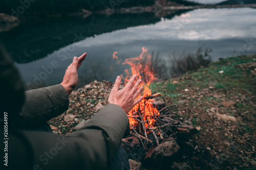 Leinwandbild Motiv Hands of young woman warming up by camp fire. Body parts of adult female at nature. Camping.