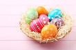 Colorful easter eggs in basket on pink wooden table