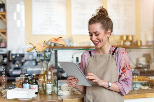 Leinwandbild Motiv Young woman using digital tablet in coffee shop