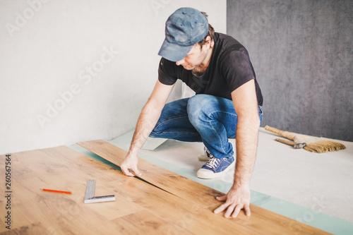 European man working at home - laying new laminate flooring - 260567564