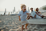 Young family with toddler children having fun on beach on summer holiday.