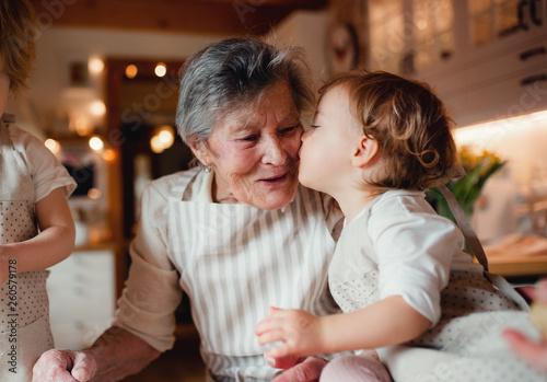 Leinwandbild Motiv Senior grandmother with small toddler children making cakes at home.