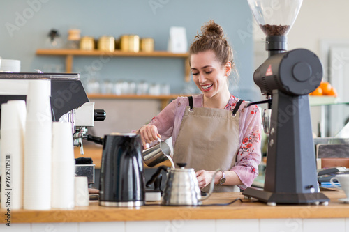 canvas print picture Female barista making coffee