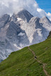 Quadro Hikers making their way through the Italian Dolomites with mighty Marmoleda mountain in the background