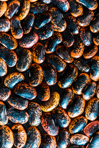 a heap of black-brown beans on black background