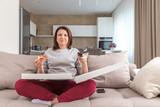 Dziewczynka jedzenie pizzy siedzi na kanapie i oglądanie telewizji w nowoczesnym mieszkaniu