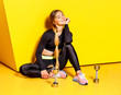 Leinwandbild Motiv Beautiful slender girl with long blond hair dressed in a stylish sportswear is sitting on the yellow floor next to the dumbbells by the yellow wall.
