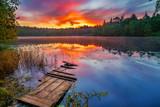 Bright sunrise over forest lake