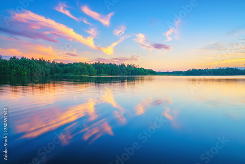 Beautiful landscape with colorful sunset over forest lake