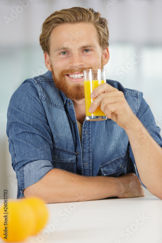 canvas print picture smiling young man drinking orange juice