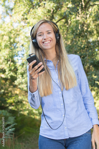 young woman listening enjoying music in forest