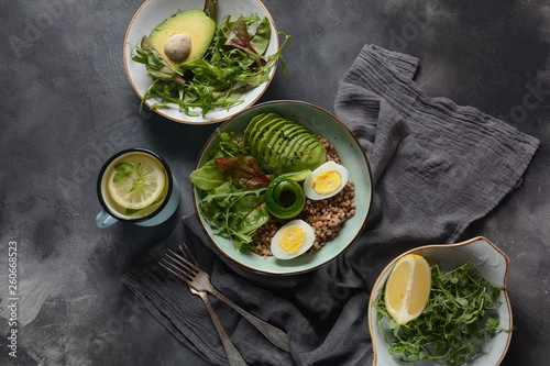 Vegan Buddha bowl with buckwheat, avocado, boiled eggs, cucumber, arugula beet leaves. Diet, detox, healthy food concept - 260668523