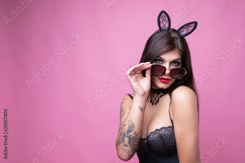 Leinwandbild Motiv Cute sexy brunette with hooked ears of hare and sunglasses poses on pink background
