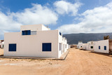 Empty street with sand and white houses in Caleta de Sebo on the island La Graciosa