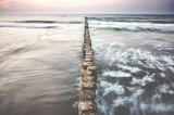 Wooden sea breakwater at sunset, color toning applied, long exposure.