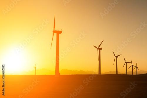 fototapeta na ścianę Big wind turbines in the desert at sunset background