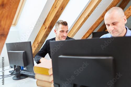 fototapeta na ścianę Zwei Kollegen arbeiten Seite an Seite am Computer
