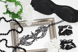 Black lace eye mask, vintage frame, lingerie, white flowers and a string of black pearls. Flat lay for magazines and fashion blogs.