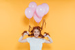 happy redhead girl with balloons tied to hair posing isolated on yellow