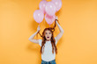 surprised redhead girl with balloons tied to hair looking at camera and posing isolated on yellow