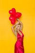 Sexy Blond Woman In Elegant Red Dress Is Holding Heart Shaped Balloons Over Her Head
