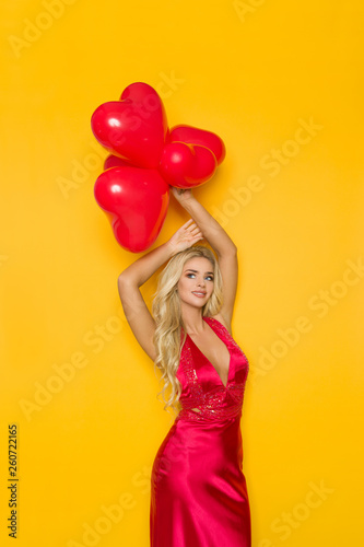 canvas print picture Sexy Blond Woman In Elegant Red Dress Is Holding Heart Shaped Balloons Over Her Head