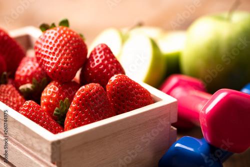 Apple, strawberry, dumbbells, on wooden table - 260744975