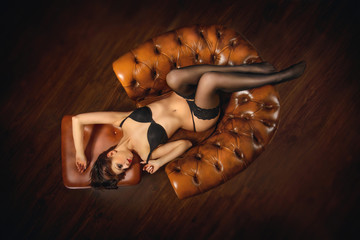 sexy woman lies in leather chair
