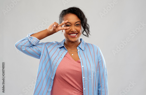 canvas print picture people and gesture concept - happy african american young woman showing peace hand sign over pink background