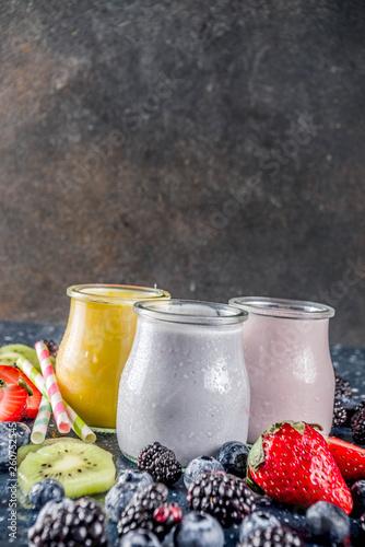 Summer fruits and berries smoothie drink. Vitamin diet snack beverage, with blueberries, strawberries, blackberries, kiwi. Dark blue concrete background copy space © ricka_kinamoto