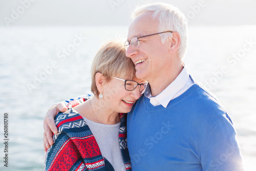 Leinwanddruck Bild Senior couple is laughing, smiling at sea beach outdoor. Happy man and woman are hugging, embracing, enjoying retirement. Concept of wellbeing, happiness, male and female health, lifestyle moments.