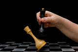 A hand with a black king knocks a white king on a chessboard. Concept - political confrontation