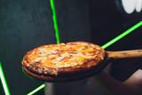 Parująca gorąca smaczna margarita Włoska pizza świeża z pieca do pizzy w pizzerii serwowana na długiej desce z drewnianą deską z copyspace.