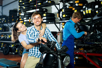 Cheerful couple sitting on motorcycle at service point