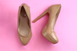 Trendy glamour fancy beige nude pink patent glossy pair of elegant  high heeled shoes on pink background