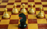 Chess set on the chess board. With selective focus on black  knight