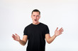 Attractive surprised man standing and looking at camera dressed in black shirt on white background.