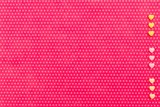 Yellow and pink small hearts on the right vertical line on the textile background, fuchsia with a print in white polka dots. View from above.