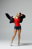 Hip hop dancer moving and jumping in photostudio