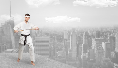 Young karate trainer doing karate tricks on the top of a metropolitan city
