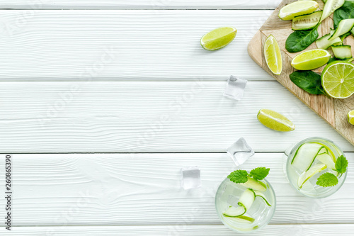 Leinwandbild Motiv summer cocktails for freshness with lime, mint, cucumber and spinach and ice on white background top view mockup