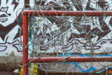 barbed wire fence with graffiti on the wall