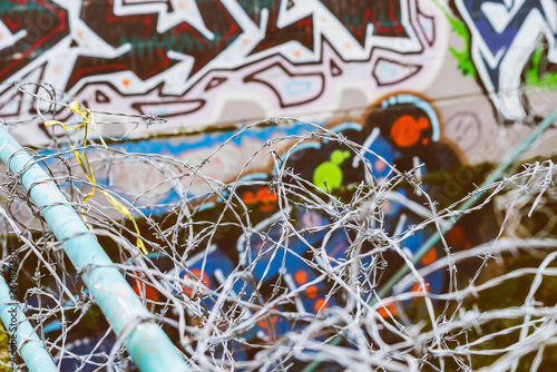 barbed wire fence with graffiti on the wall - 260870301